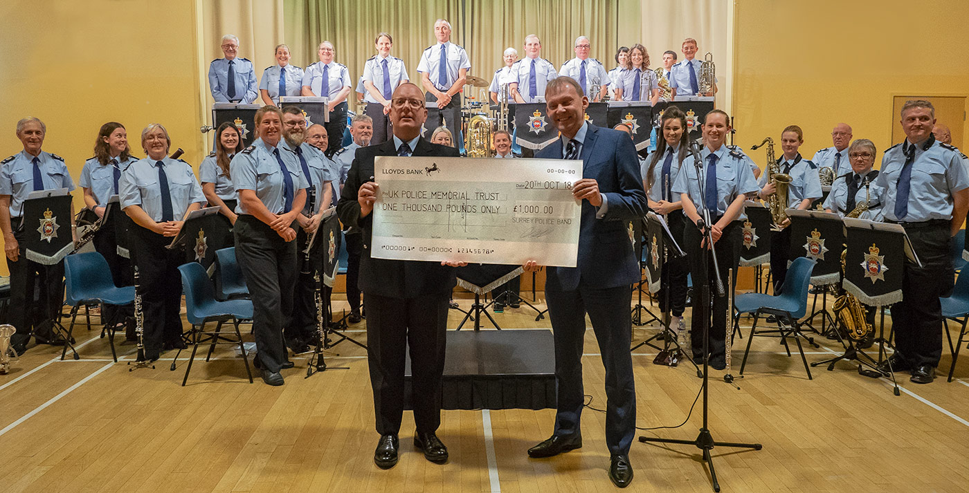 Chris Webb from the UK Police Memorial receiving a cheque from Surrey Police Band Musical Director Graham Atterbury.